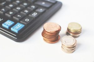 Coins kept beside a calculator to reduce cost per lead