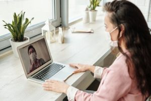 Woman videocalling while wearing facemask